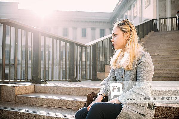 Junge Frau sitzt auf einer Stadttreppe und schaut weg  Mailand  Italien