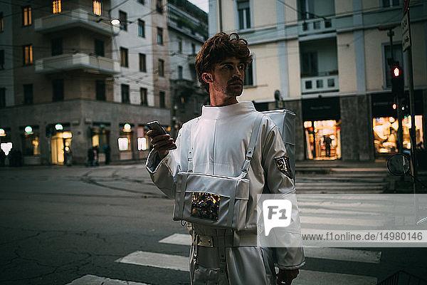 Astronaut mit Smartphone auf Fußgängerüberweg