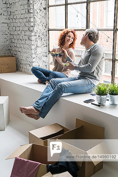 Couple moving into industrial style apartment  sitting on window ledge eating takeaway meal