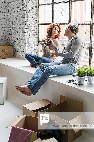 Ehepaar zieht in eine Wohnung im Industriestil  sitzt am Fensterbrett und isst Essen zum Mitnehmen