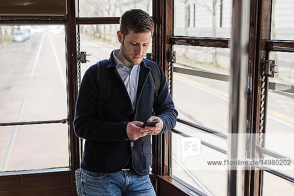 Mann benutzt Smartphone in Straßenbahn  Mailand  Lombardei  Italien