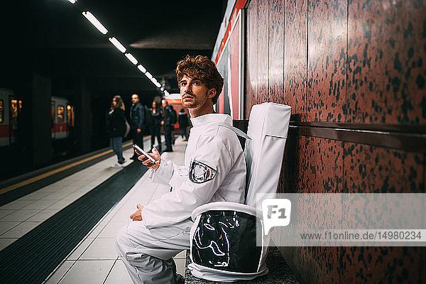 Astronaut mit Smartphone auf dem Bahnsteig