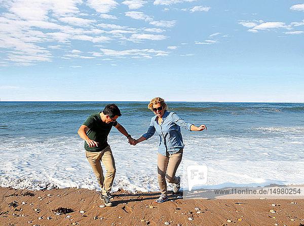 Paar spielt am Strand  Thurlestone  Devon  Vereinigtes Königreich