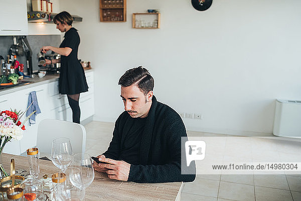 Businessman using smartphone  colleague making coffee in background