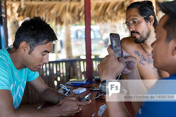 Freunde benutzen Smartphone in Strandhütte  Pagudpud  Ilocos Norte  Philippinen