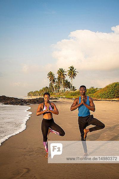 Paar praktiziert Yoga am Strand