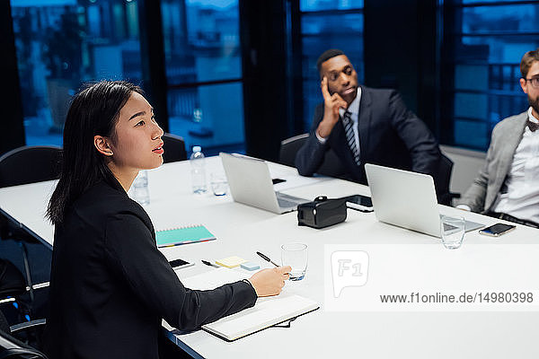Businesswoman and men having listening during conference table meeting