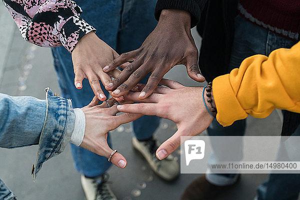 Vier weibliche und männliche junge erwachsene Freunde bringen die Hände zusammen  Nahaufnahme der Hände