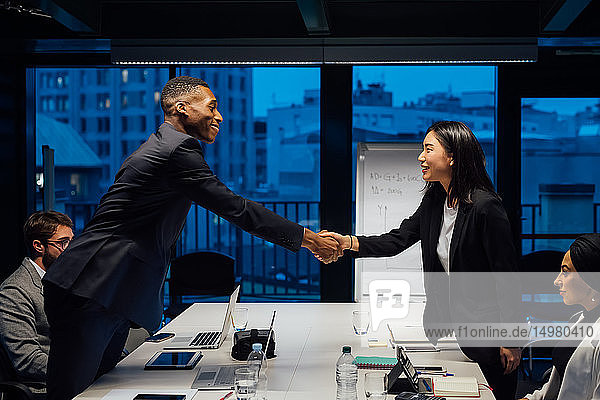 Businesswoman and male client shaking hands over conference table meeting