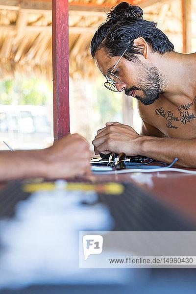 Mann benutzt Smartphone in Strandhütte  Pagudpud  Ilocos Norte  Philippinen