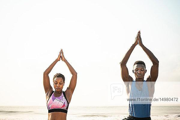 Couple practising yoga on beach