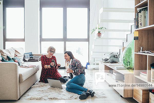 Girlfriends talking and using smartphone on floor in loft office