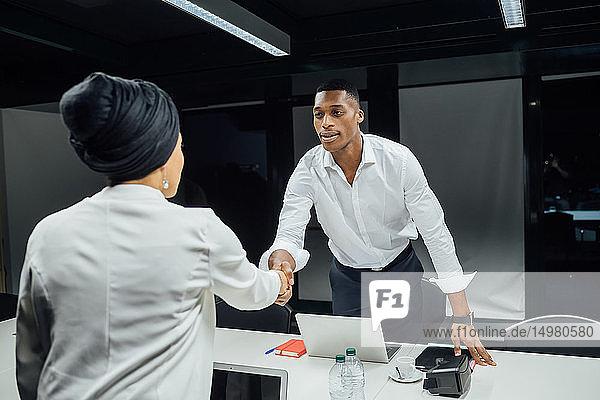 Geschäftsmann und -frau schütteln Hände über Konferenztisch