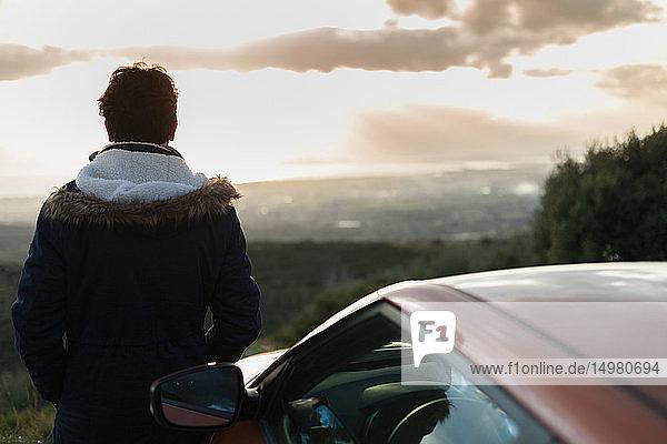 Man resting against car on roadside  enjoying view on hilltop