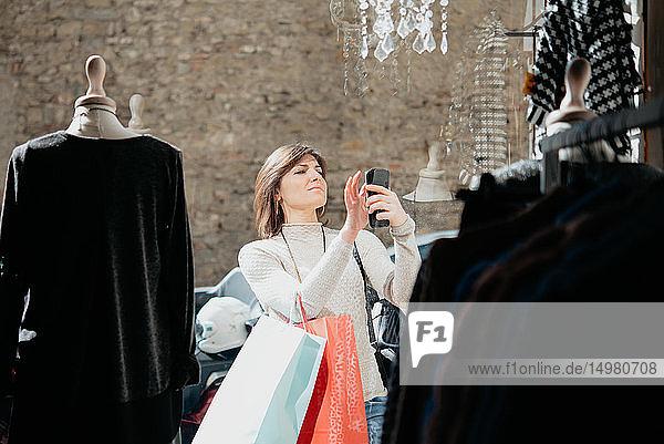 Weibliche Käuferin beim Fotografieren vor einer Modeboutique
