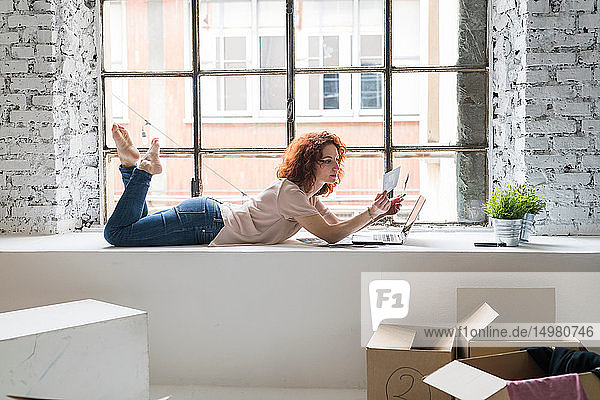 Mid adult woman moving into industrial style apartment  lying on window ledge looking at photograph