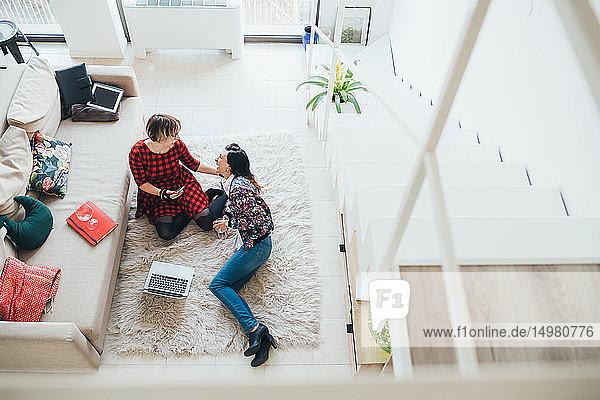 Girlfriends talking on floor in loft office