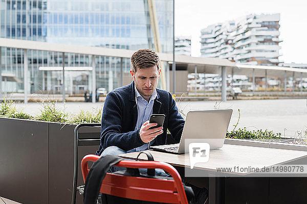 Mann mit Smartphone und Laptop im Café  Mailand  Lombardei  Italien
