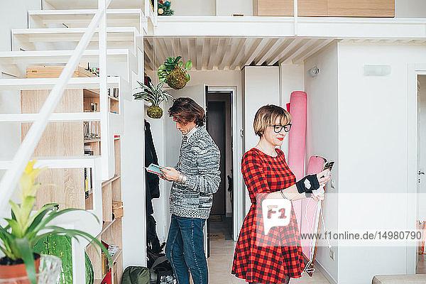 Woman using smartphone  man reading book in loft office