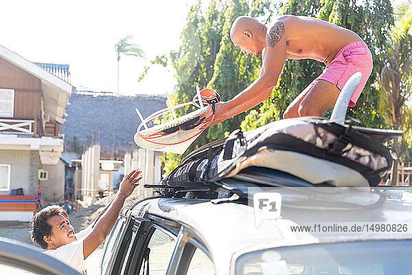 Mann hilft Freund beim Verladen von Surfbrettern auf das Fahrzeug  Pagudpud  Ilocos Norte  Philippinen