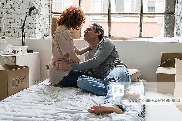 Couple moving into industrial style apartment  on mattress gazing at each other
