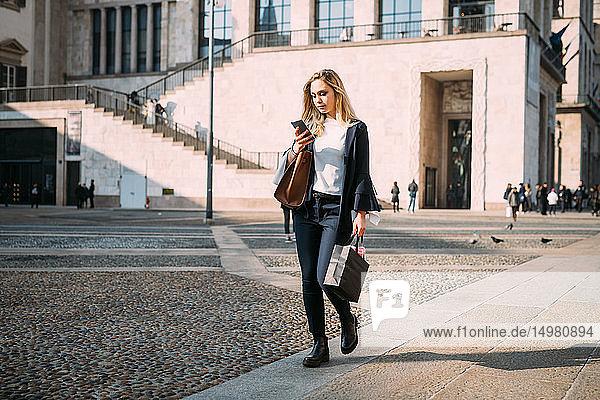 Junge Frau schlendert über den Stadtplatz und sieht sich ein Smartphone an