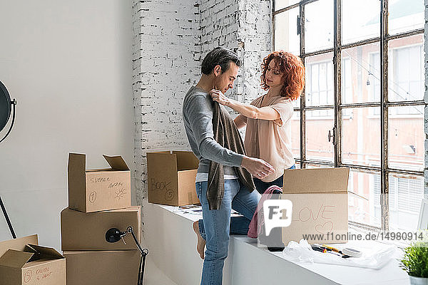Romantic couple moving into industrial style apartment  unpacking sweaters from cardboard box