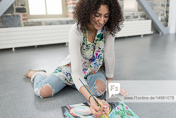 Junge Malerin malt Leinwand auf Atelierboden