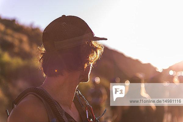 Mann mit Baseballmütze schaut einer Gruppe von Menschen über die Schulter  Sonnenuntergang