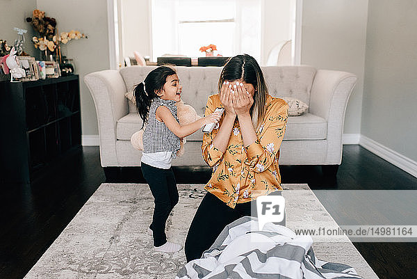 Girl playing hide and seek with mother in living room