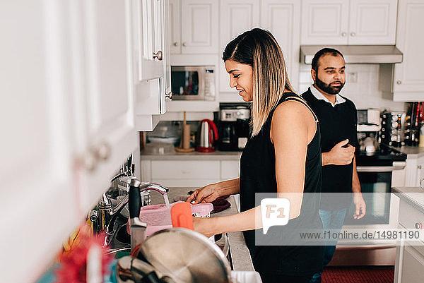 Mittleres erwachsenes Paar in der Küche beim Geschirrspülen