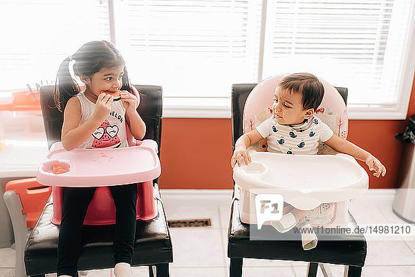 Girl eating water melon in high chair looking at baby brother