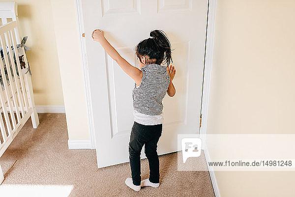 Mädchen öffnende Kinderzimmertür  Rückansicht