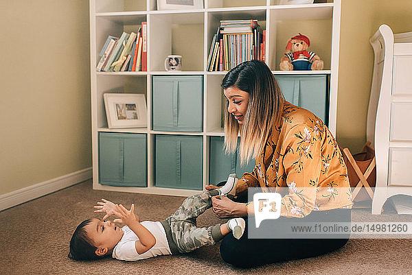 Mother sitting on nursery floor putting socks on baby son