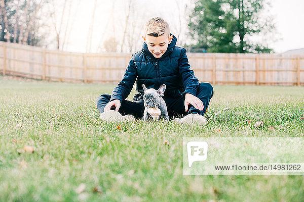 Junge spielt mit Welpe auf Rasen