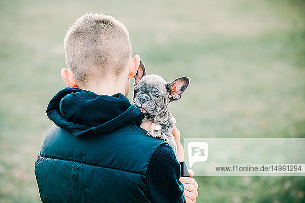 Junge trägt Welpen ins Freie