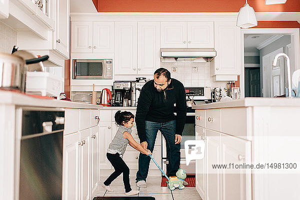 Girl playing with push toy in kitchen  father watching