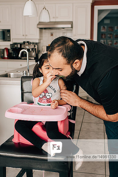 Girl in high chair feeding water melon to father