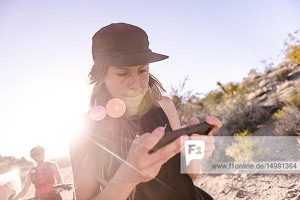 Frau bedient Drohne (unbemanntes Luftfahrzeug) mit Smartphone auf ländlichem Feldweg