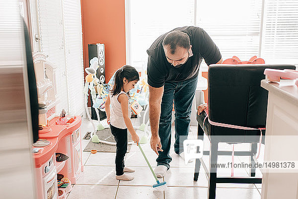 Girl sweeping kitchen floor  father watching