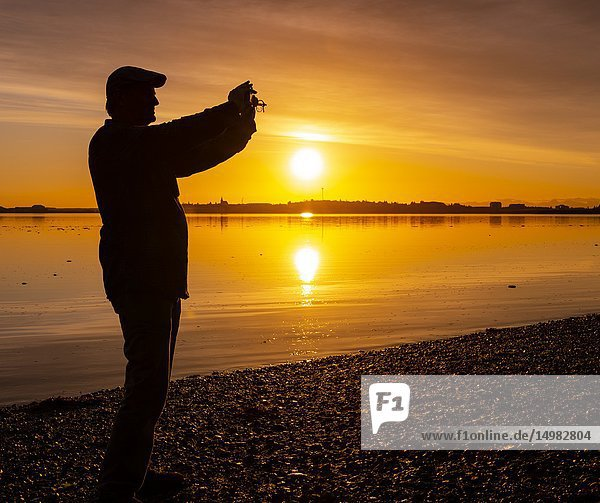 Man taking a picture at sunset  Borgarnes  Western Iceland.