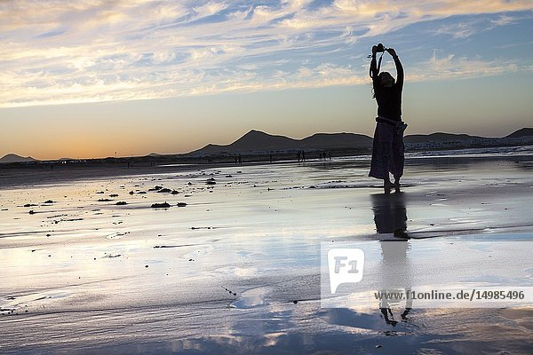 Reflection of woman and cloudscape in a low tide at the beach at sunset. Famara  Lanzarote. Spain.