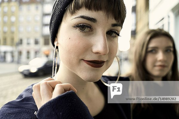Woman with individual style and big earrings next to friend  in city Cottbus  Brandenburg  Germany.