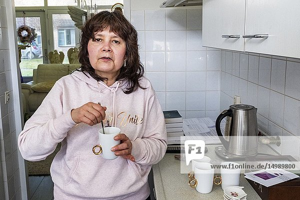 Dongen  Netherlands. Middle aged woman preparing for an alternative spiritual service inside the residential kitchen of her Spiritual Leader  drinking a cup of tea.