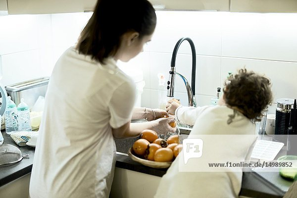 Mother and toddler watching khaki fruits in kitchen at home  in Munich  Germany.