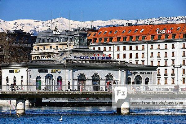 City center of Geneva - landmark - exhibition center Cité du Temps on the bridge Pont de la Machine  Geneva  Switzerland  in background Jura mountains in snow  France  Europe