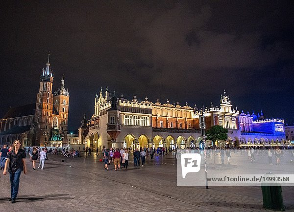 People walking around the Main Market Square of Krak—w Old Town at night as light illuminate the exterior of Church of Our Lady Assumed into Heaven (St. Mary's Basilica) and Krak—w Cloth Hall  Lesser Poland Voivodeship  Poland.