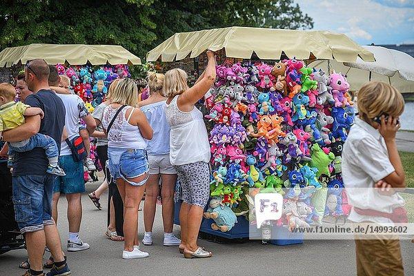 Women browse the plush dragon dolls on street vendor cart  Kraków  Lesser Poland Voivodeship  Poland.