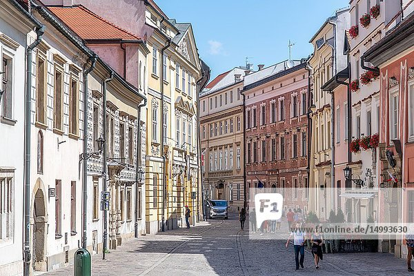 View looking down cobblestone street lined with historic townhouses in Main Market Square of Krak—w Old Town  Lesser Poland Voivodeship  Poland.