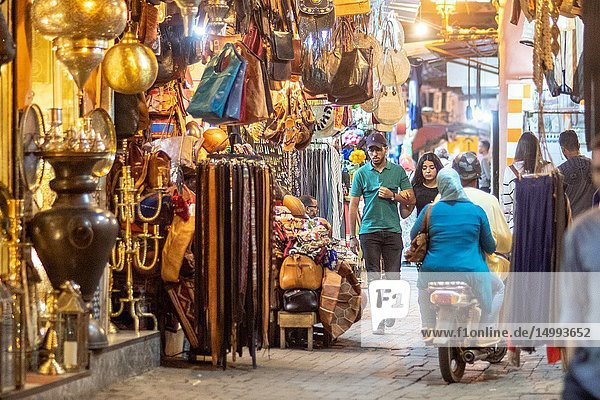 Shoppers walk the streets of medina quarter of Marrakesh at night past shop-fronts selling textiles and leather goods  Morocco.